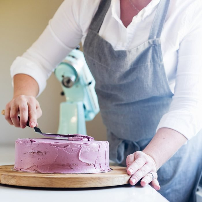 trim the cream icing on a lilac cake with a spatula; Shutterstock ID 411716662; Job (TFH, TOH, RD, BNB, CWM, CM): Taste of Home