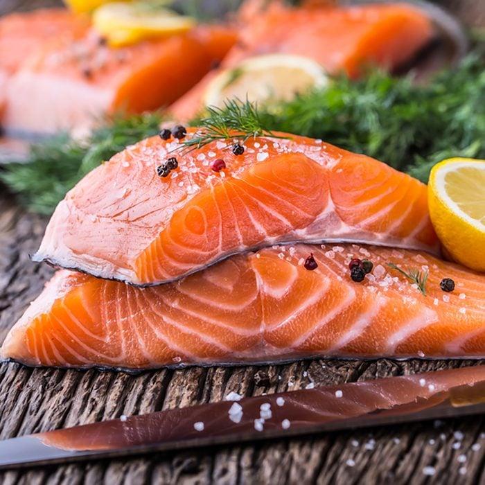 Raw salmon fillets pepper salt dill lemon and rosemary on wooden table