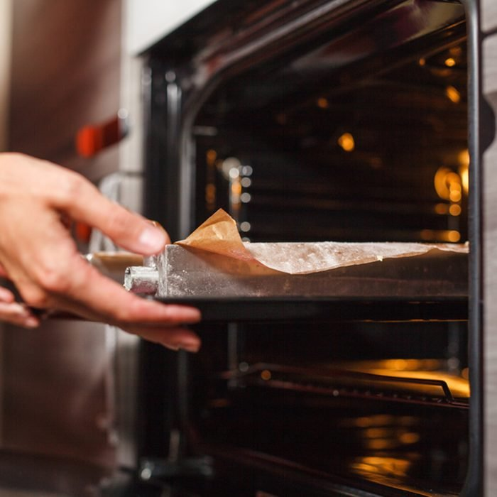 Woman cooking in the kitchen, puts cakes in the oven; Shutterstock ID 580824481