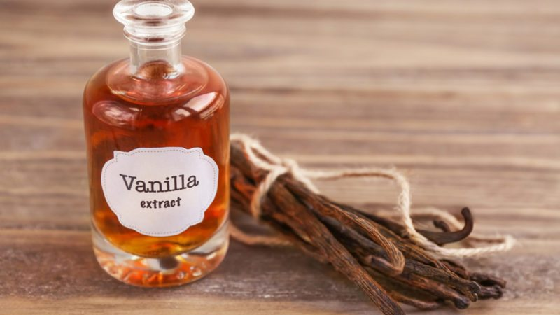 Bottle with aromatic extract and dry vanilla beans on table; Shutterstock ID 700819798