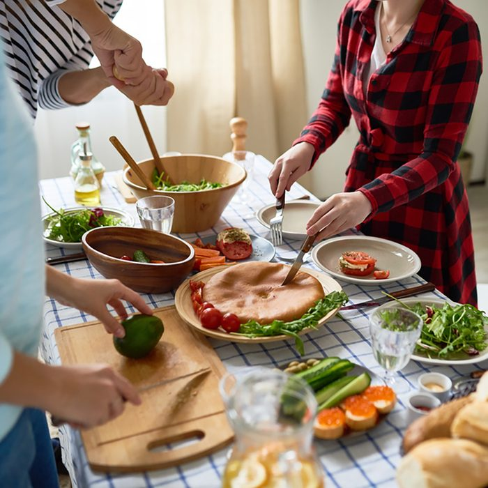Low section of unrecognizable people cutting pie and vegetables standing around dinner table with homemade food on it