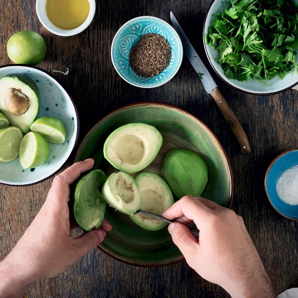 Cooking of Mexican guacamole sauce. Man preparing Mexican sauce guacamole on rustic wooden table