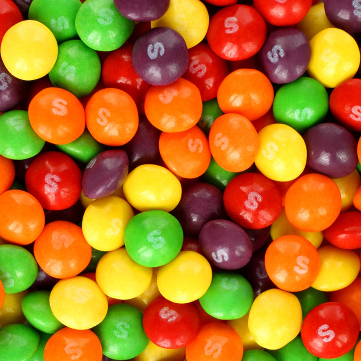 Skittles multicolored fruit candies background.