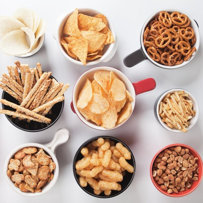 Potato chips,pretzels, roasted peanuts and other salty snacks over white background