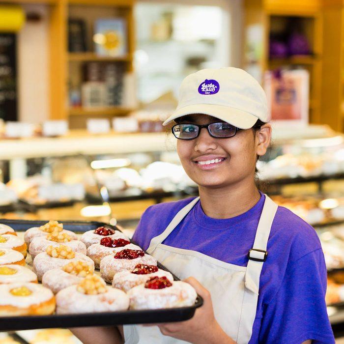 Baker holding tray of treats at Sugar Plum Bakery