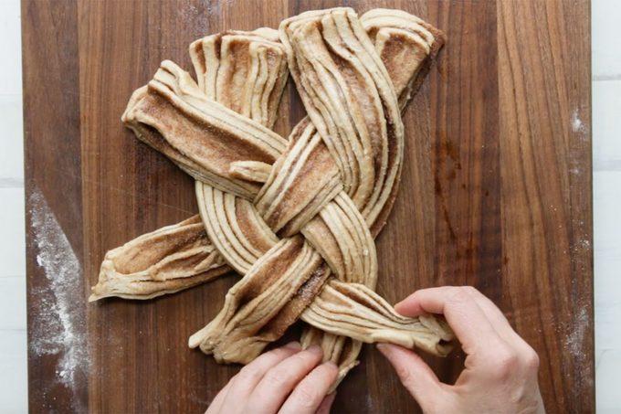 Twisting cinnamon roll dough