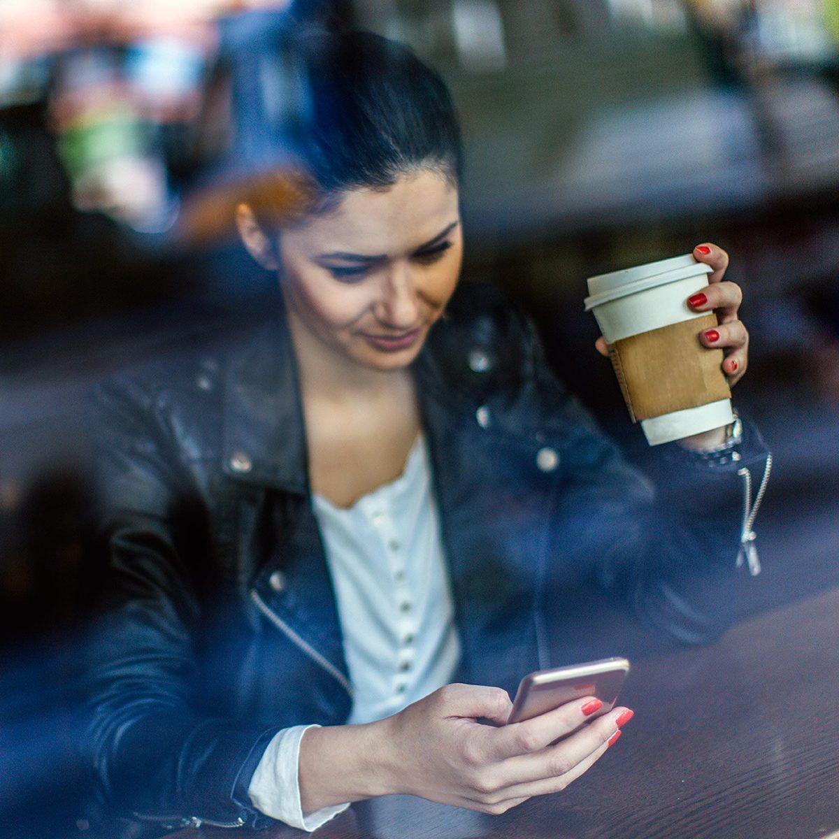Woman drinking coffee while on phone