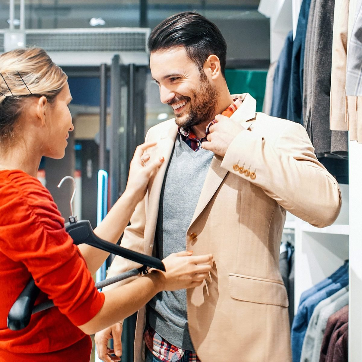 Woman helping man put on a blazer