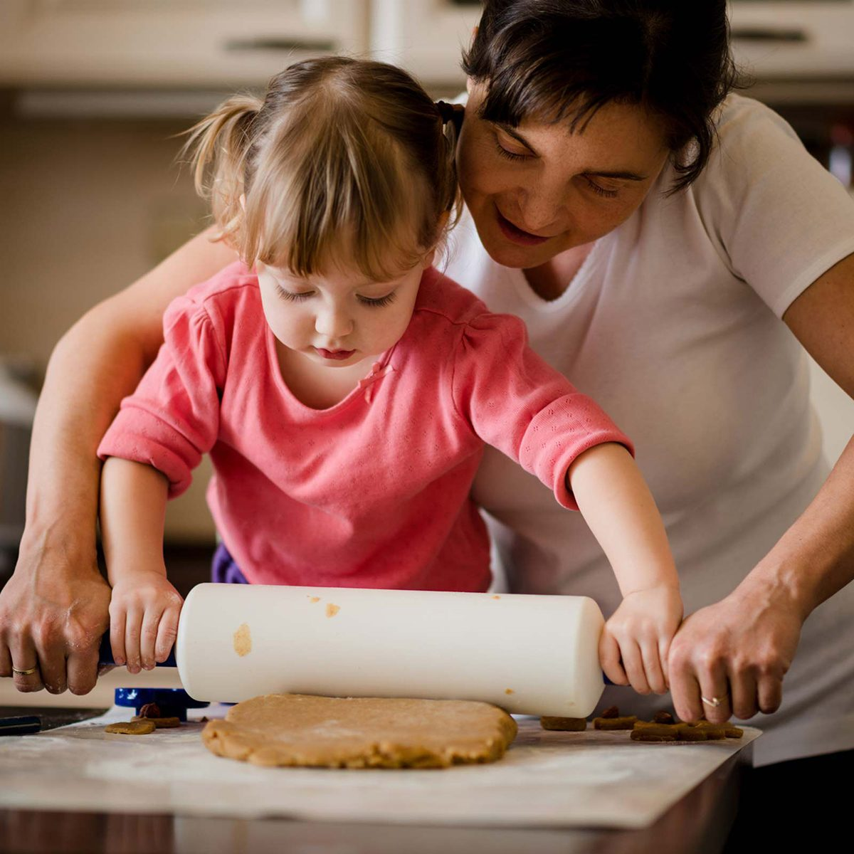 Mother and daughter rolling out dough
