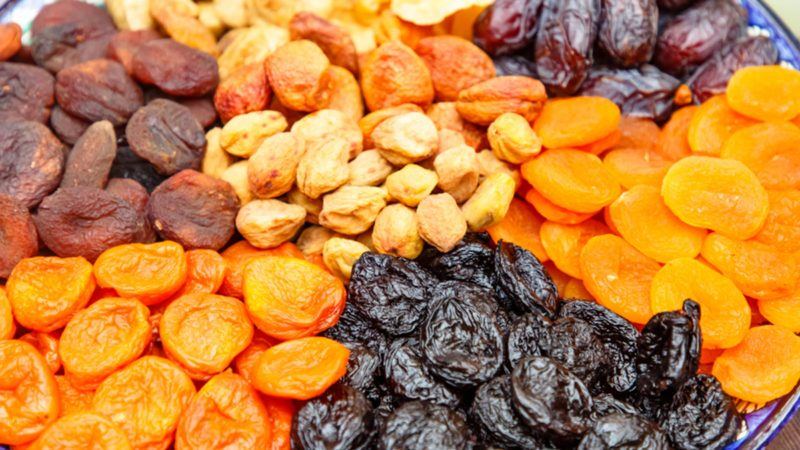Dried fruits: dried apricots, prunes and others lie on a plate