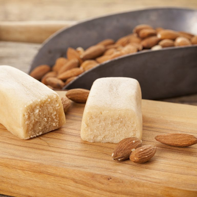 Marzipan bar and almonds on rustic table