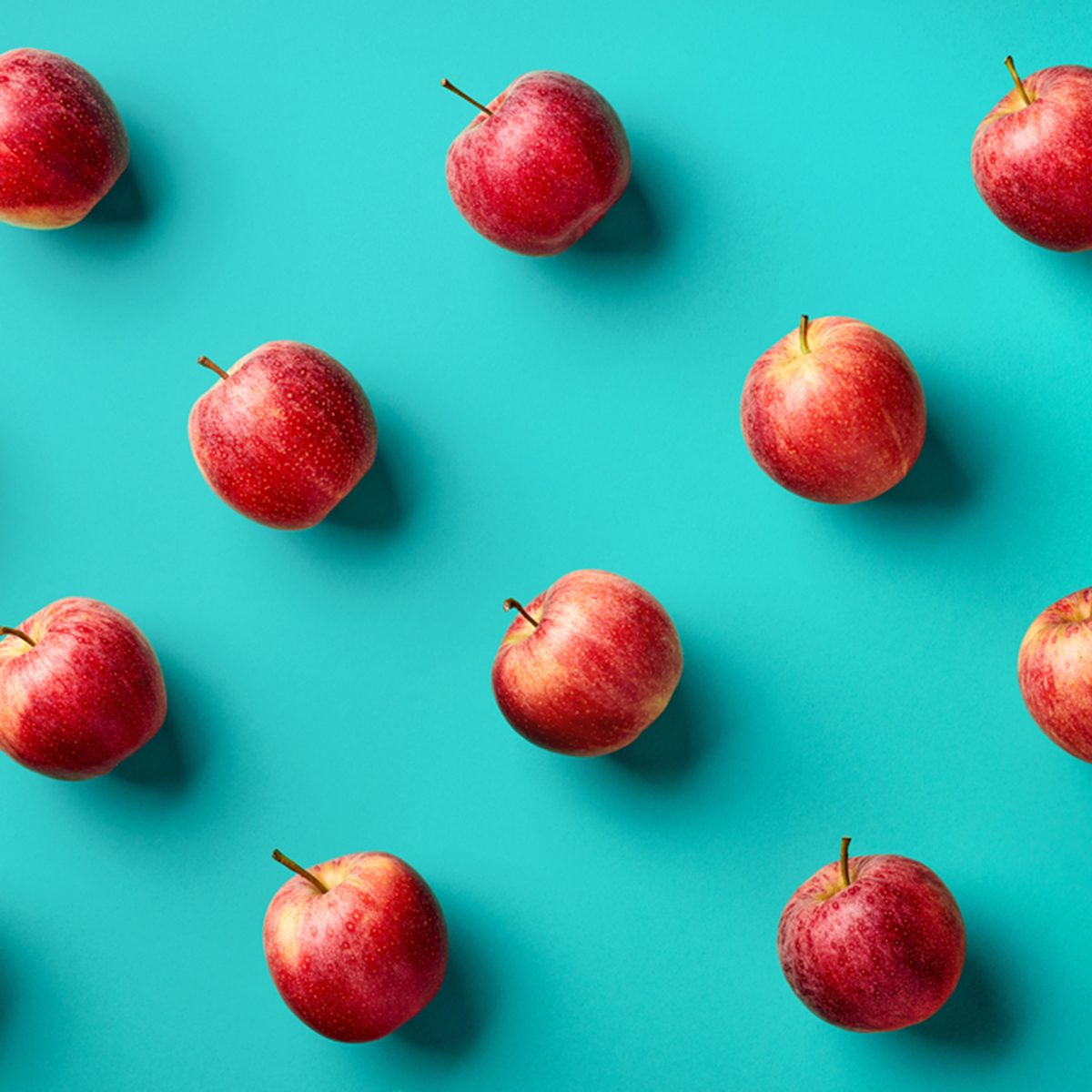 Colorful fruit pattern of fresh red apples on blue background.