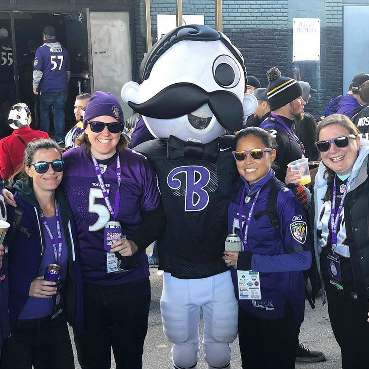 Baltimore Ravens fans posing with mascot
