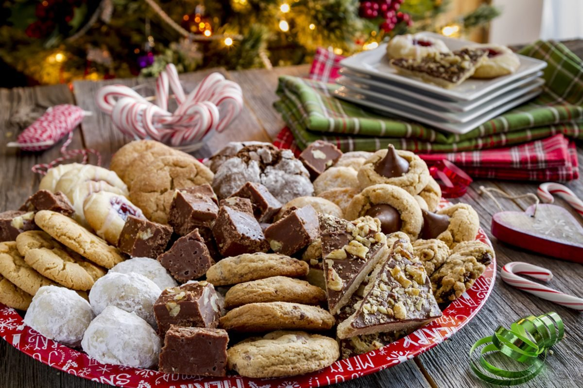 Holiday cookie party table with large platter filled with homemade cookies and candies