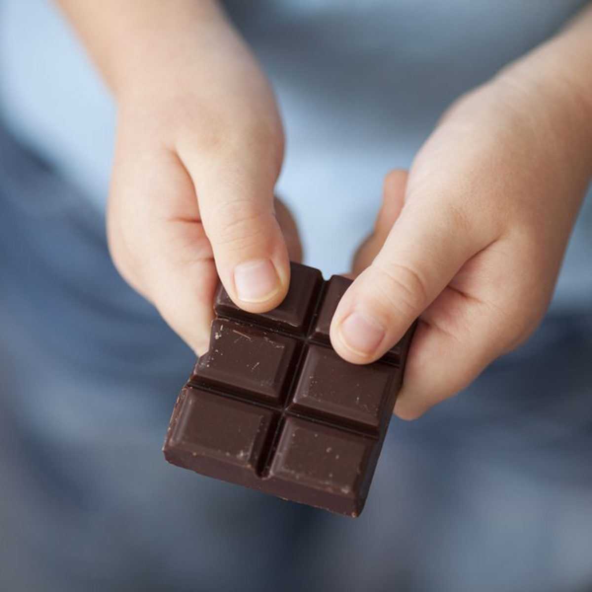 Child breaking off piece of chocolate bar