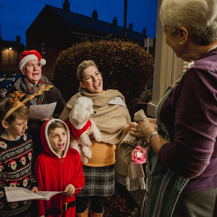 Three generation family are doing door-to-door carol singing. There is a senior woman at the door, appreciating their singing.; Shutterstock ID 672017275; Job (TFH, TOH, RD, BNB, CWM, CM): TOH