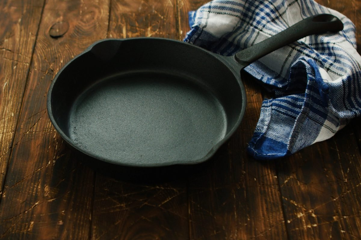 Simple black colored cast iron pan with checkered towel on wooden shabby table surface