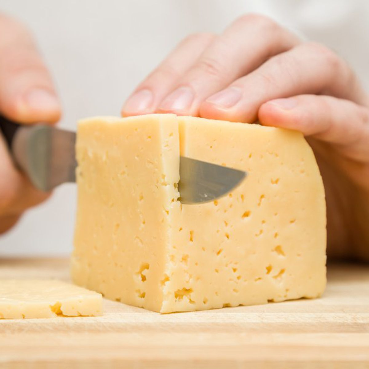 Chef cutting block of cheese