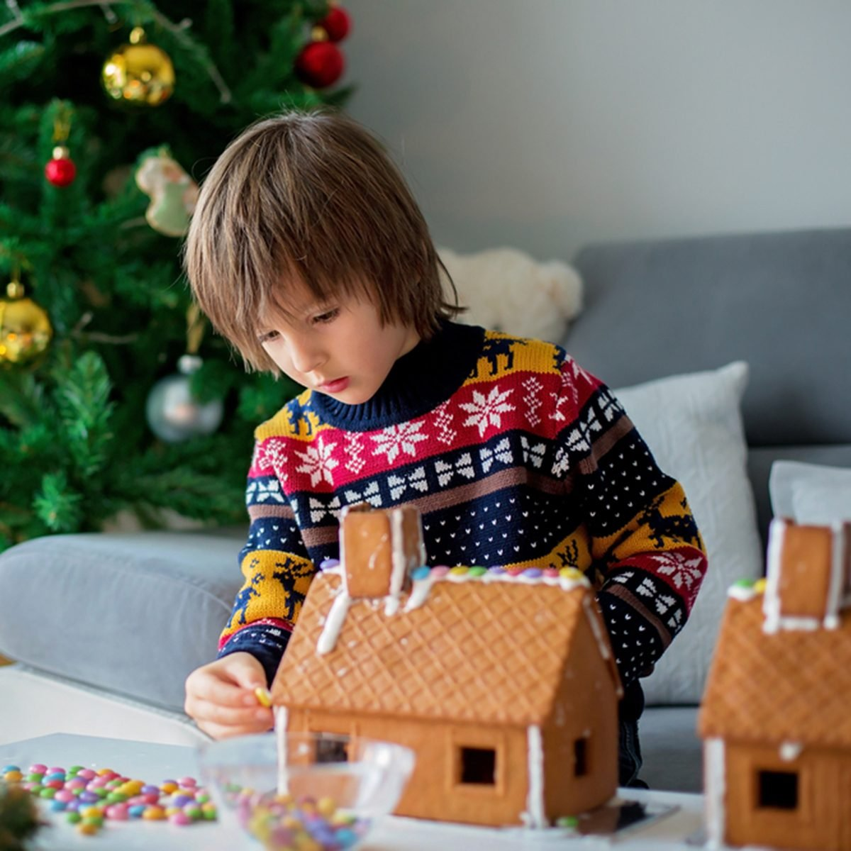 Adorable preschool child, boy, decorating gingerbread houses for Christmas at home