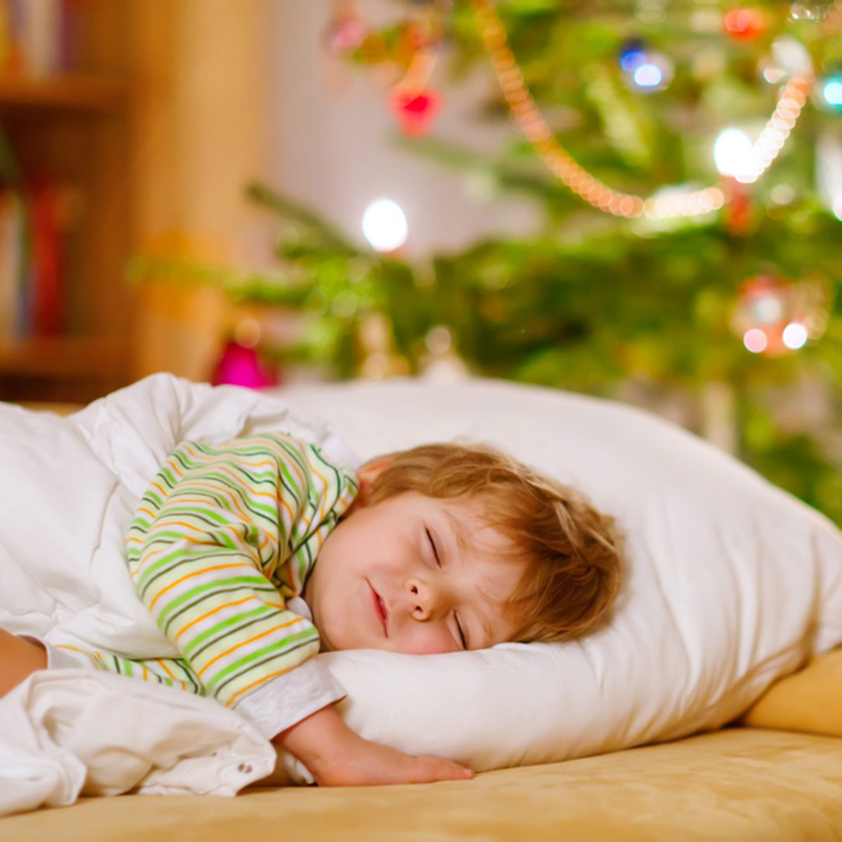 Little cute blond boy sleeping under Christmas tree and dreaming of Santa at home
