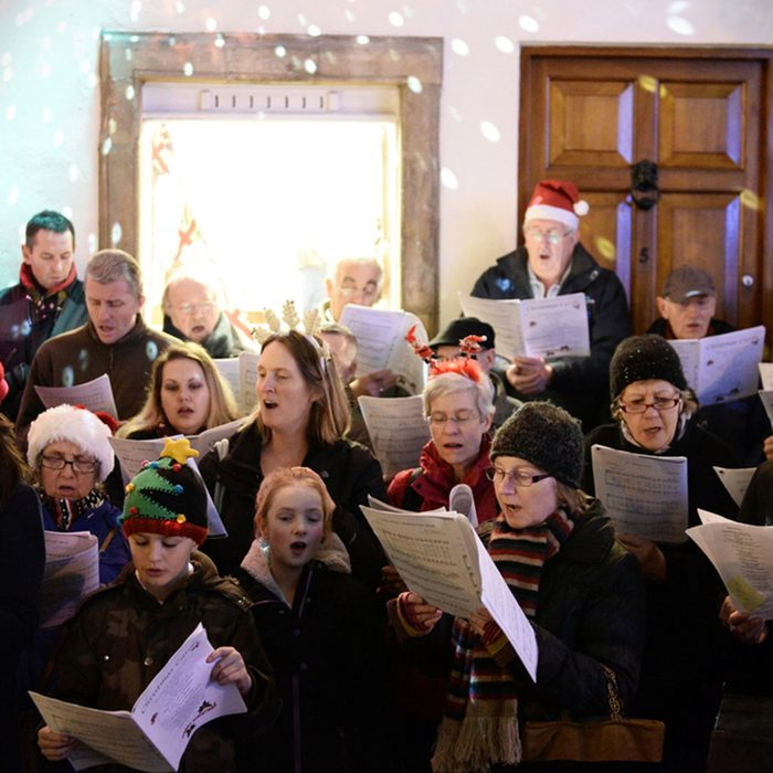 People sing carols at the Christmas Market in the streets surrounding Bath Abbey