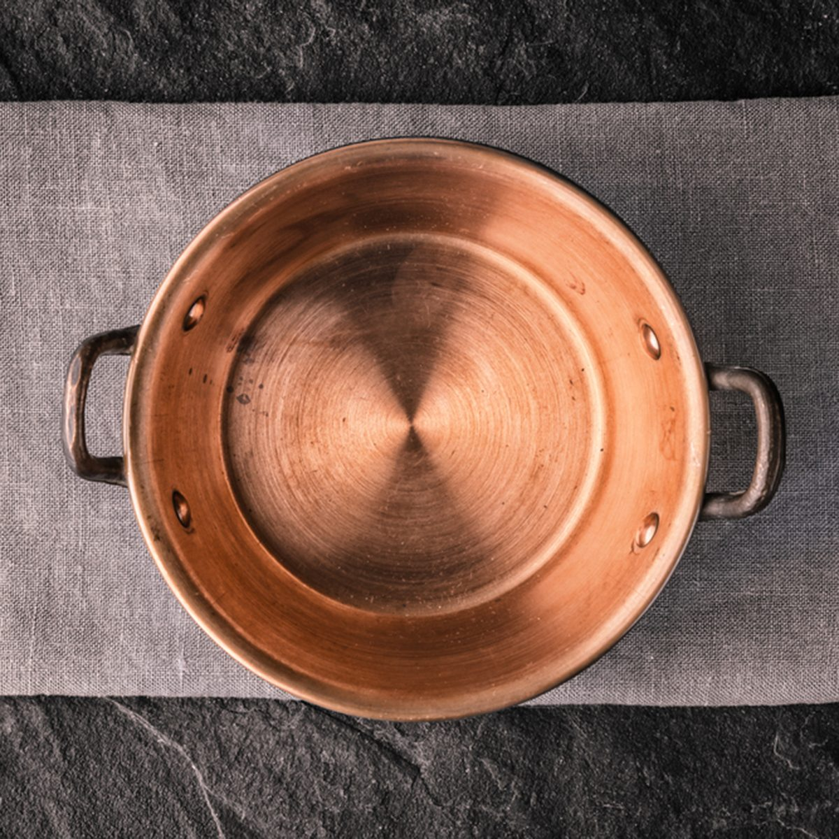 Copper pot on the dark stone table top view; Shutterstock ID 395567689; Job (TFH, TOH, RD, BNB, CWM, CM): TOH