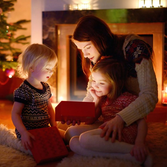 Young mother and her two little daughters opening a magical Christmas gift by a Christmas tree in cozy living room in winter; Shutterstock ID 212733760; Job (TFH, TOH, RD, BNB, CWM, CM): TOH