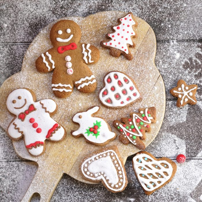 Christmas cookies of various shapes in sugar glaze on a cutting board on a brown wooden table sprinkled with flour, flat lay.