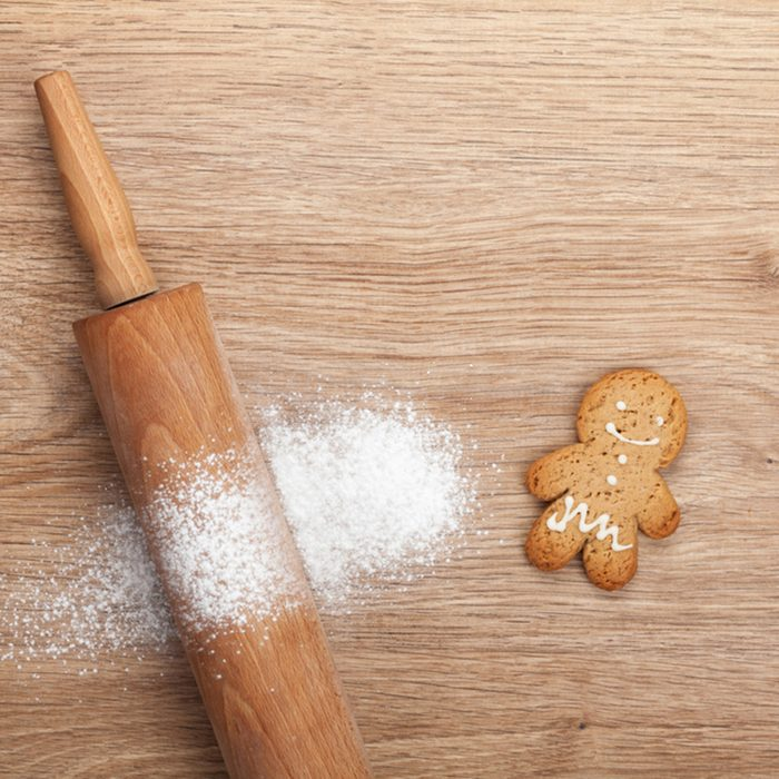 Rolling pin with flour and gingerbread cookie on wooden table.