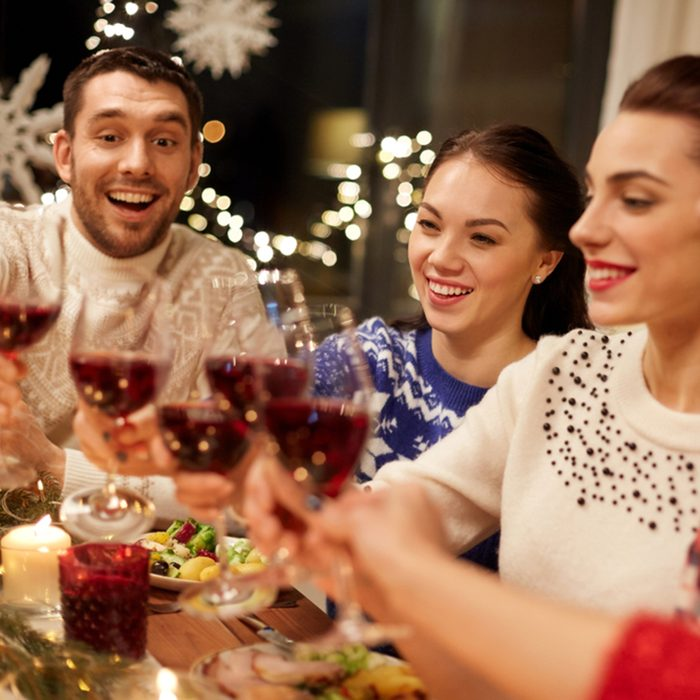 happy friends having christmas dinner at home, drinking red wine and clinking glasses