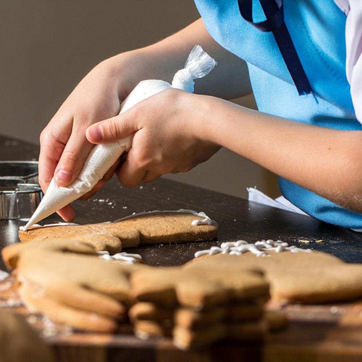 kids hand decorating cookies with sugar.