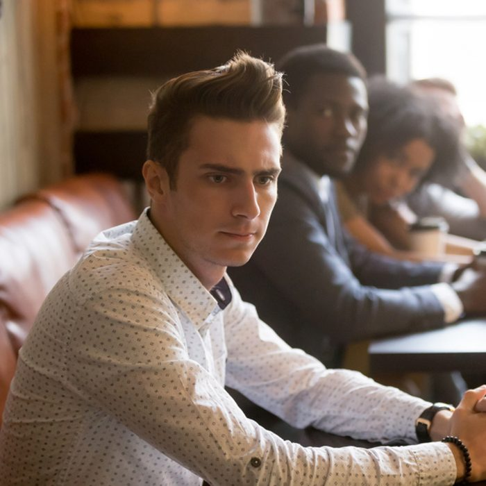 Diverse people looking at thoughtful frustrated man in cafe
