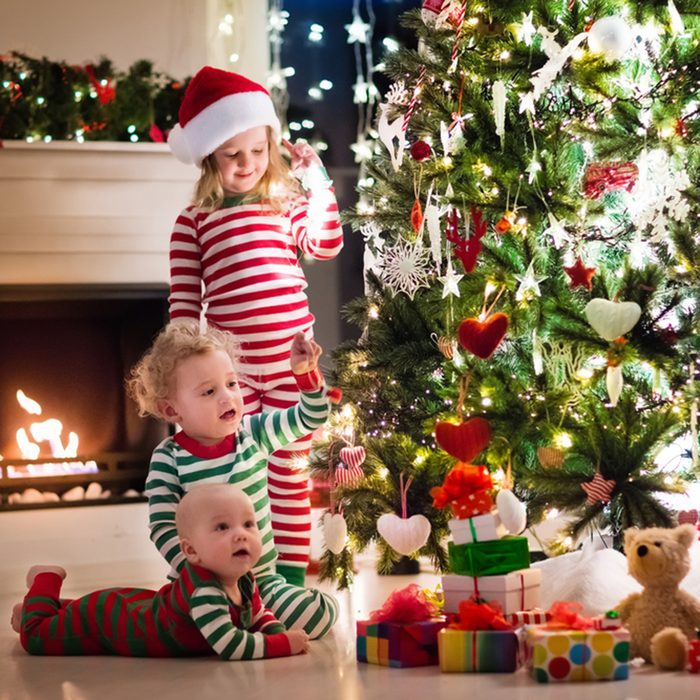 Happy little kids in matching red and green striped pajamas decorate Christmas tree in beautiful living room with traditional fire place.