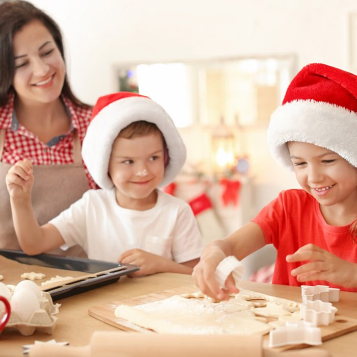 Mother and children making Christmas cookies together at home