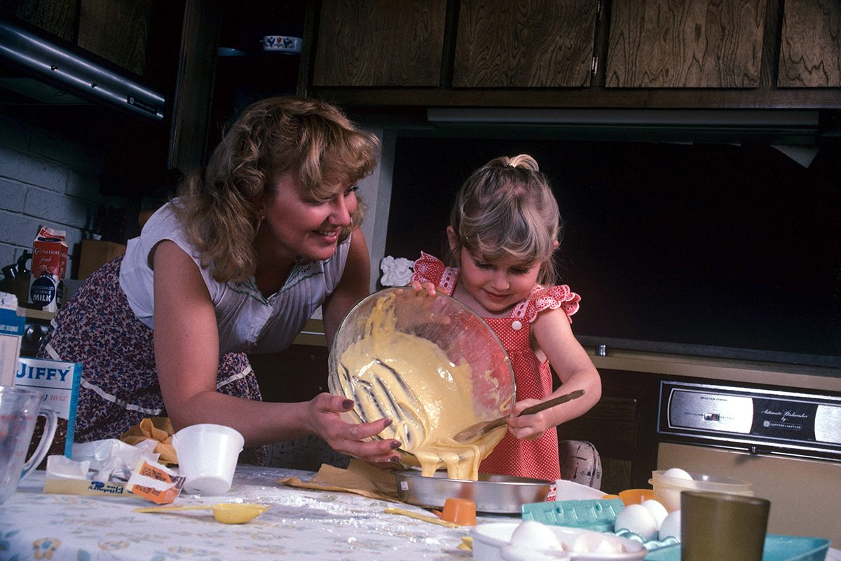 Child cooking helped by her mother