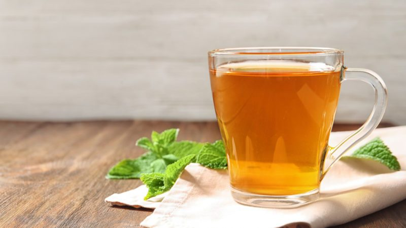 Cup with hot aromatic mint tea on wooden table
