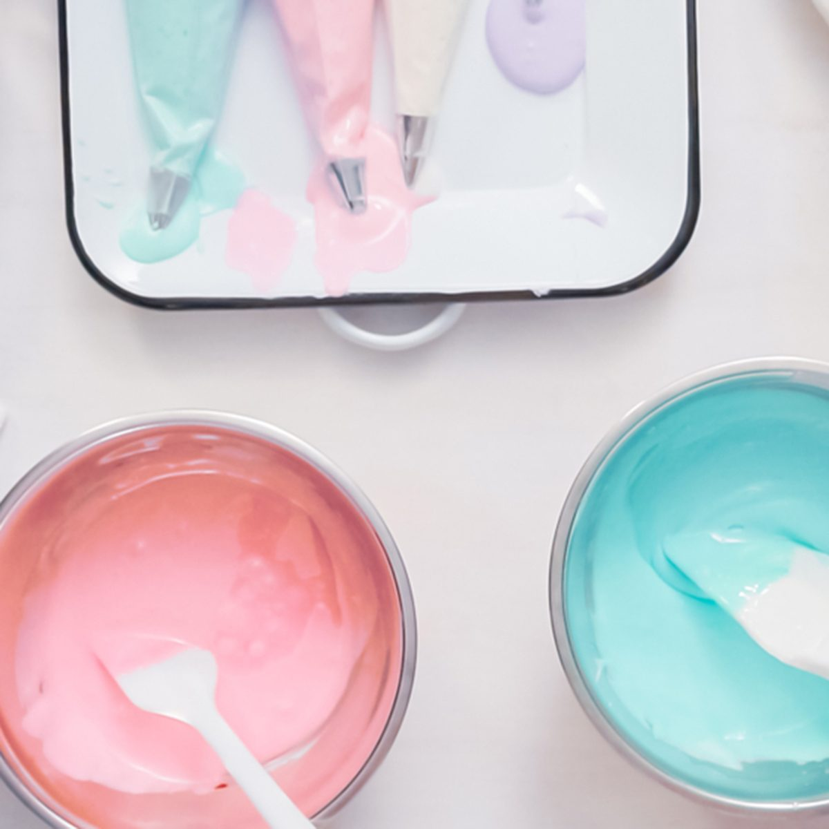 Mixing food coloring into royal icing to decorate unicorn sugar cookies.
