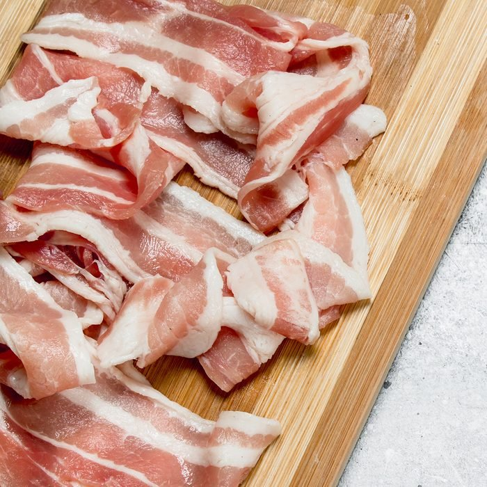 Raw bacon on the Board. On a rustic background.