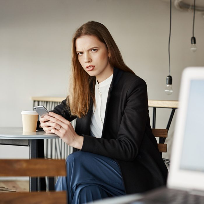 Woman is insulter with offensive words of stranger sitting with laptop.