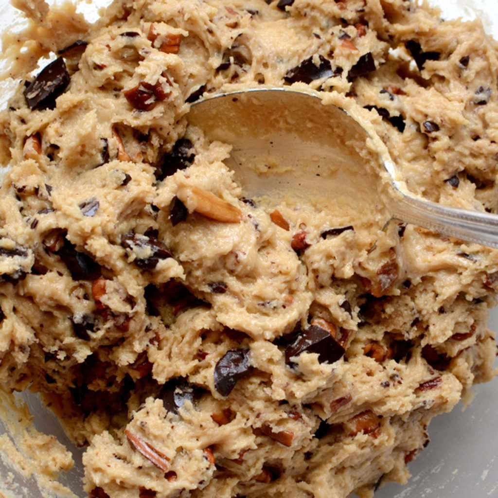 Raw cookie dough being mixed with chocolate chunks and chopped pecan nuts; Shutterstock ID 178109060; Job (TFH, TOH, RD, BNB, CWM, CM): Taste of Home