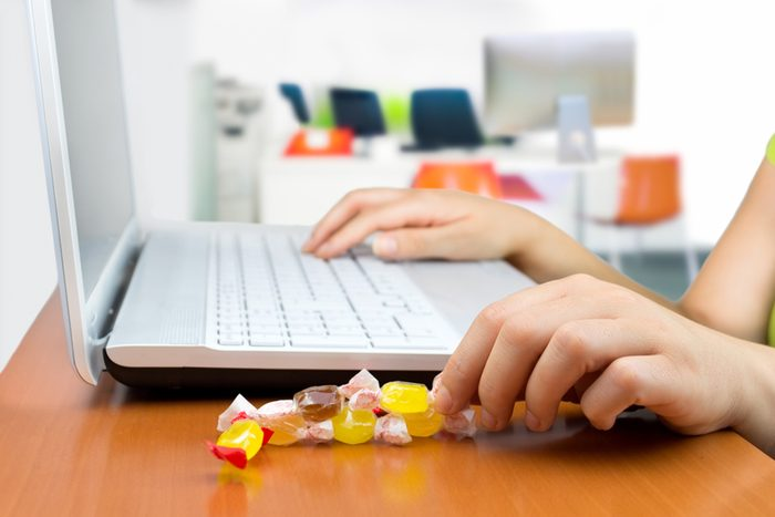woman working at the laptop eating a candy sweet; Shutterstock ID 295011389; Job (TFH, TOH, RD, BNB, CWM, CM): Taste of Home