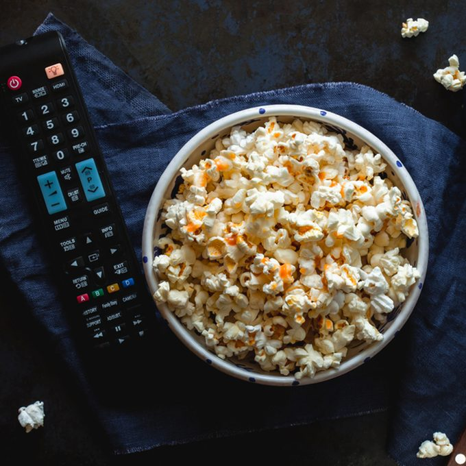 Bowl of popcorn with salted caramel, remote control TV, glass with milk on a blue tablecloth. View from above. Leisure. Watch TV.; Shutterstock ID 659564446; Job (TFH, TOH, RD, BNB, CWM, CM): TOH