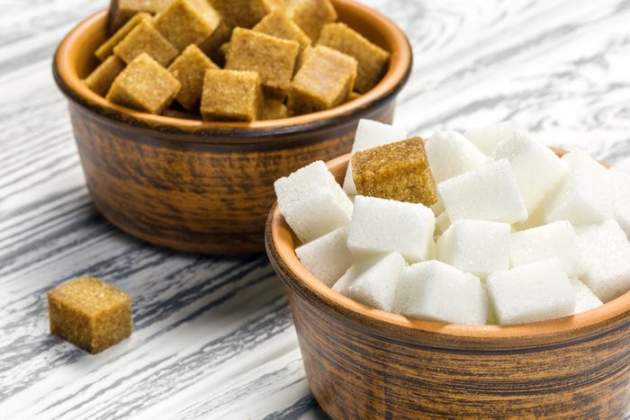White refined sugar and brown unrefined sugar cubes in ceramic bowls on a light wooden table.