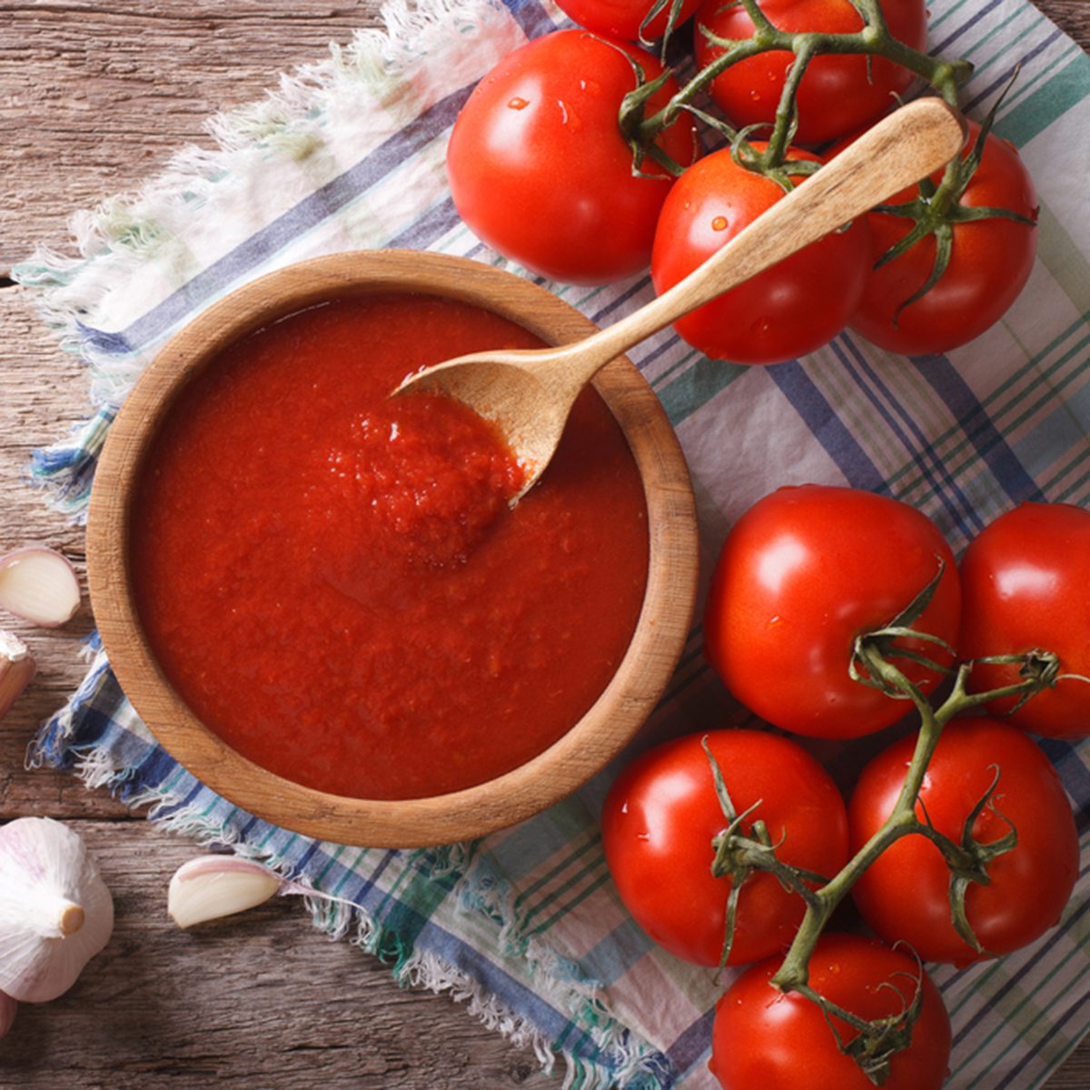 Tomato sauce with garlic and basil in a wooden bowl. horizontal view from above