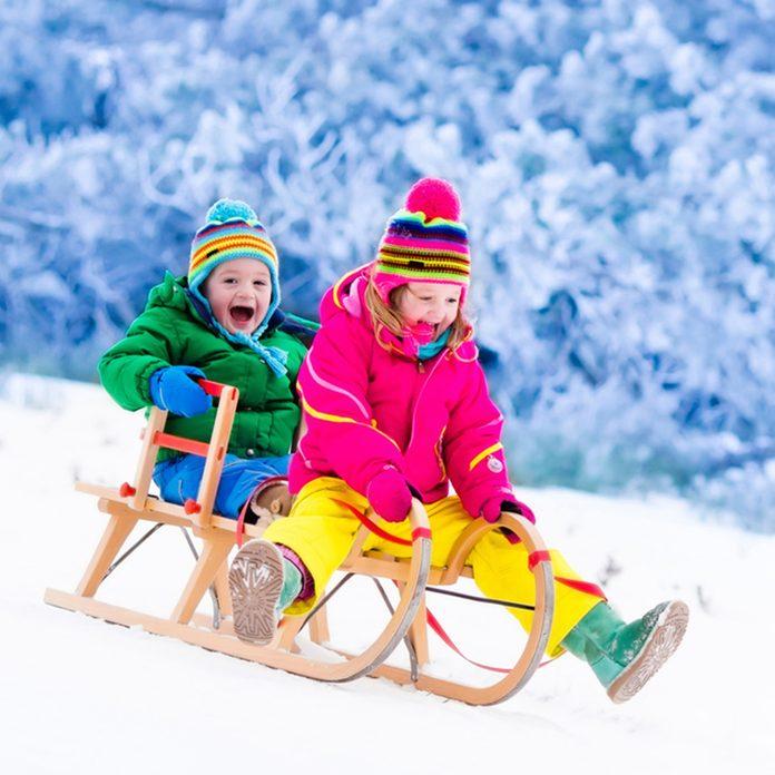 Little girl and boy enjoy a sleigh ride.