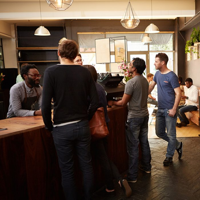People standing at the counter of a modern coffee shop