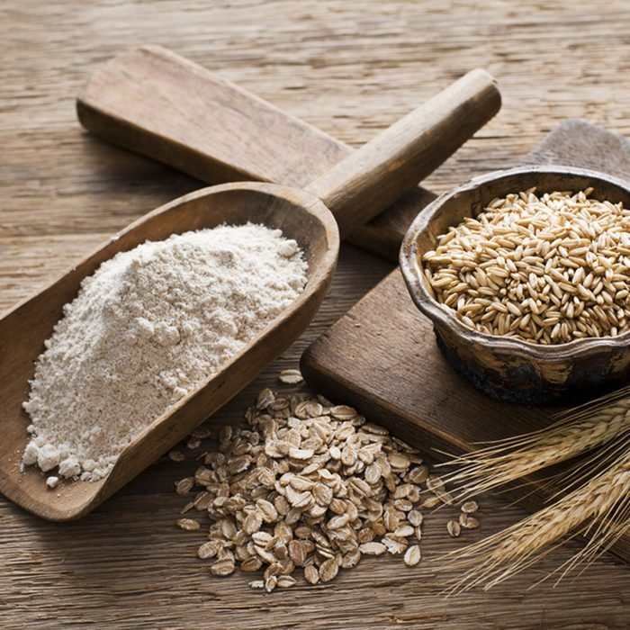 Whole grain and flour on wooden background close up
