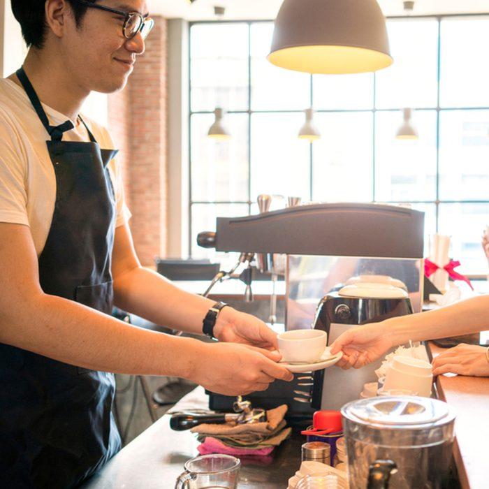 beautiful woman order a coffee to barista in a coffee shop