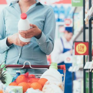 Woman doing grocery shopping at the supermarket and reading food labels