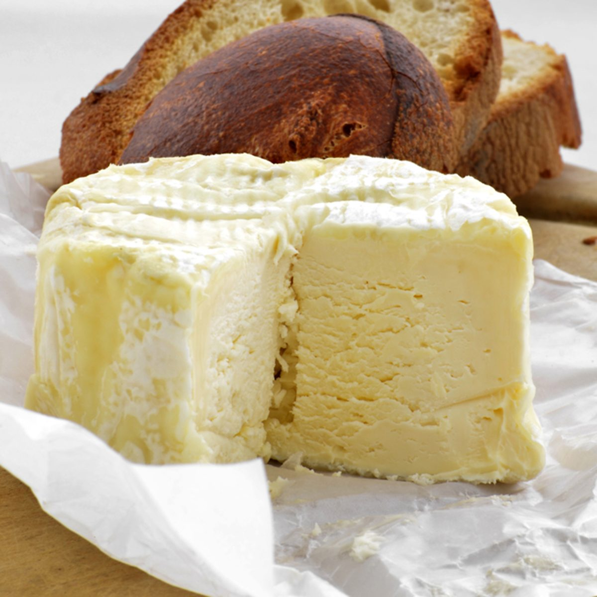 Brillat Savarin soft french cheese in waxed paper on a board with slices of rustic french bread